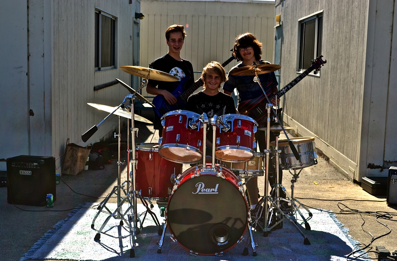 Local musicians and Palisades Elementary School alumni (L to R) Drake Abrahamsson, Chris Baker and  Michael Isacs form the band MCD. Here, the trio pauses from playing hits at the Pooper Bowl. Photo by Madison May