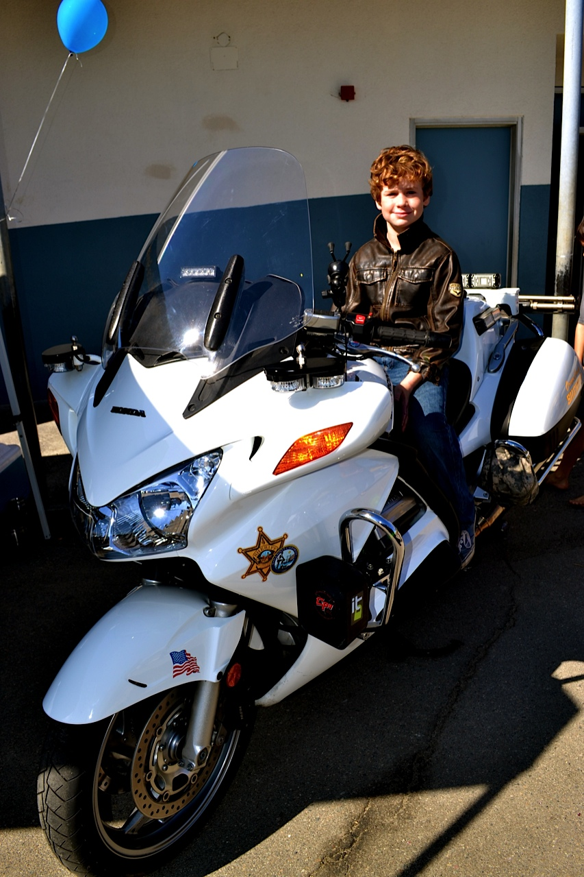 Cooper Moore rides high on an Orange County Sheriff's Department motorcycle. Photo by Madison May