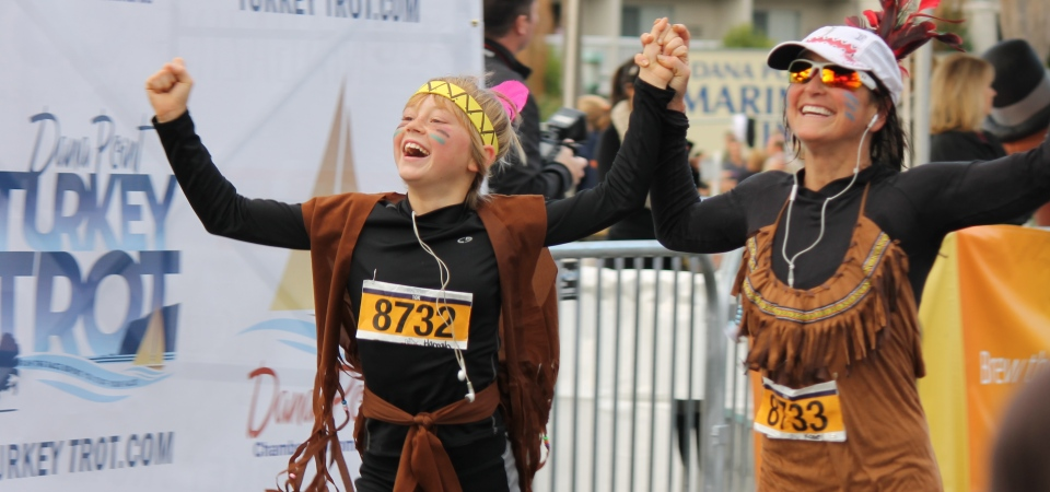 Thousands start Thanksgiving Day each year at the Dana Point Turkey Trot. Runners are shown here celebrating at the finish line during last year's event. Photo: Andrea Papagianis