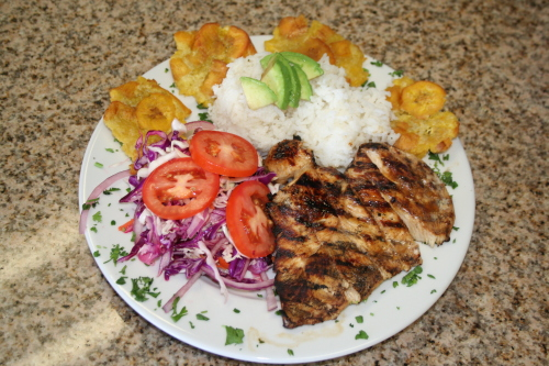 La Colombiana Pollo Asado is grilled chicken breast, marinated in citrus juices and served with plantains, rice and salad. Photo: Samantha Hammer