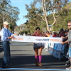 Dolores Castro of Santa Ana crosses the finish line to grab a first-place finish in the masters women's division at the Dana Point Turkey Trot. Photo: Andrea Swayne