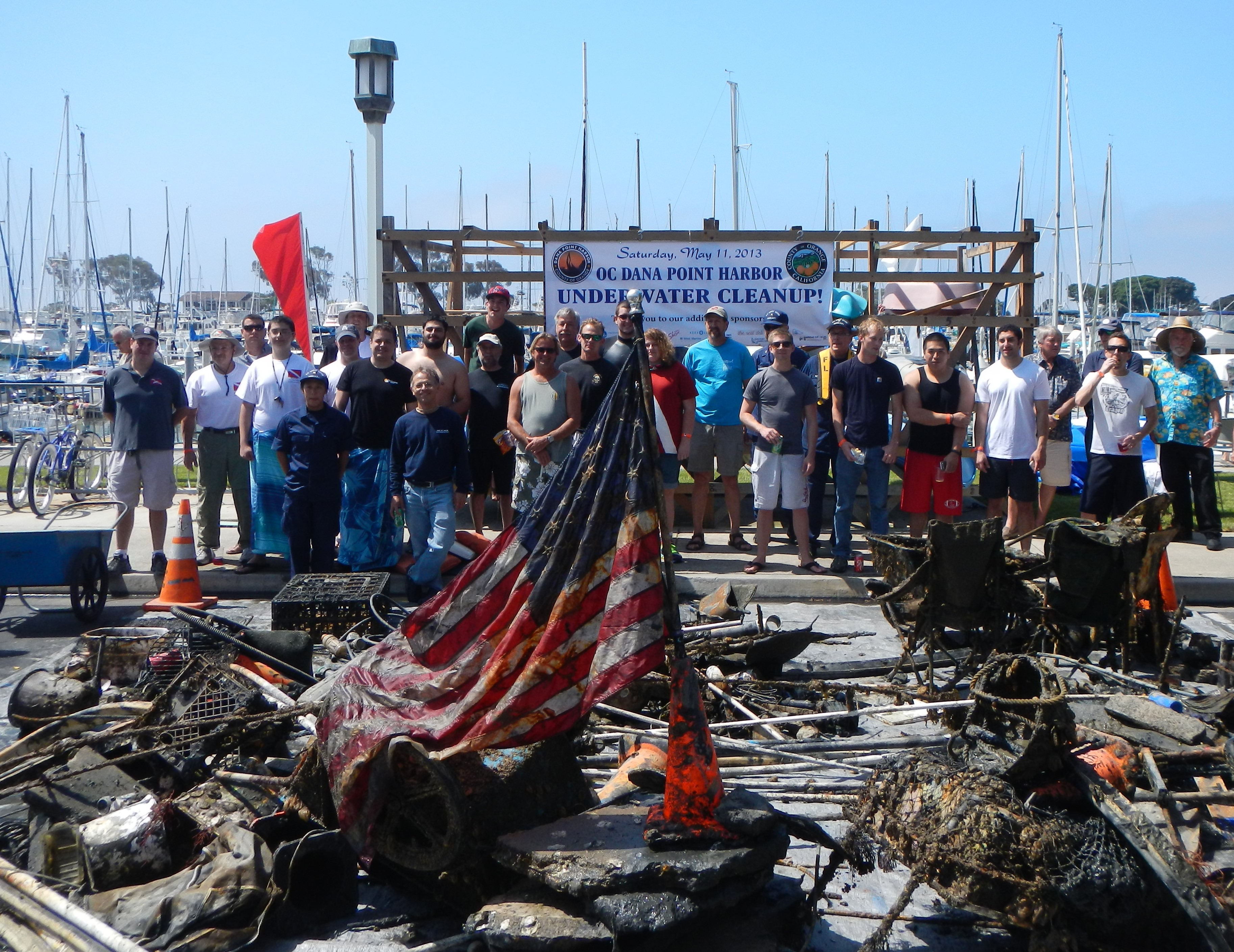 Volunteer divers at a past Dana Point Harbor Underwater Cleanup stand with piles of debris collected from the harbor floor. Photo: Courtesy