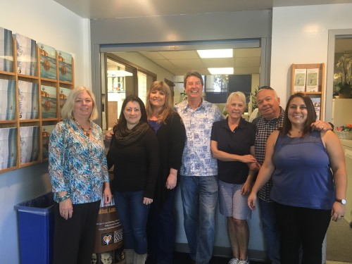 Kevin Evans (center) poses for a photo with members of his staff at the Dana Point Community Center. Photo: Andrea Swayne