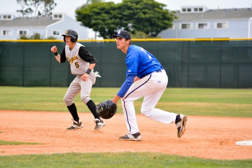 Capistrano Valley's Riley Kasper, left, gets a lead while Dana Hills first baseman Joe DeBaca readies for a pitch during a South Coast League game on May 4. Photo: KDahlgren Photography