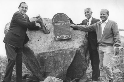 "Orange County Harbors Director Ken Sampson, County Harbor Engineer Jim Ballinger and breakwater contractor Ernie Silberberger place time capsule in rock at Dana Point Harbor, Oct. 1, 1968. A ""Rock Placing Ceremony"" marked the beginning of the construction Dana Point Harbor, Aug. 29, 1966. (Construction actually began the previous month.) At this event, material were collected for placement in a time capsule, which was placed inside the aforementioned rock on Oct. 1, 1968."