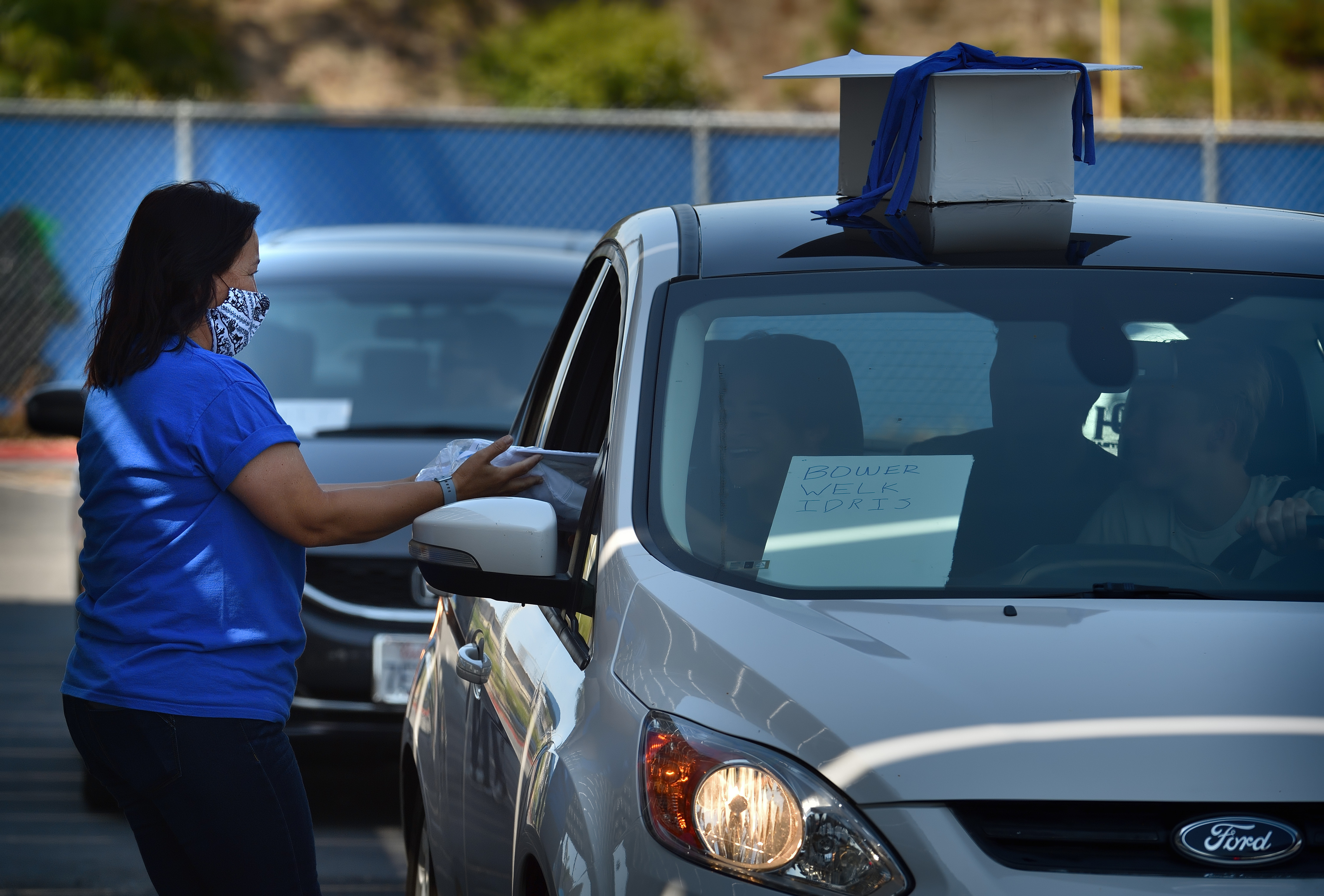 Dana Hills High School holds a small celebration as students pull up in cars to receive their cap and gown during the COVID-19 lockdown